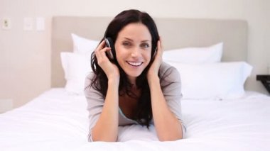 Woman on her bed moves to the music she is listening to — Wideo stockowe