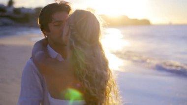 Par svarvning och kyssas under solnedgången på stranden — Stockvideo