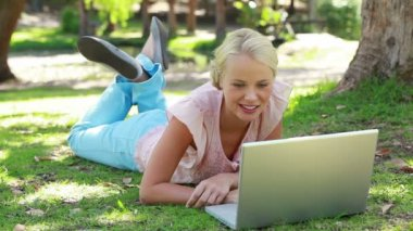 A woman lies in the park with her laptop as she laughs and then looks at the camera — Stock Video