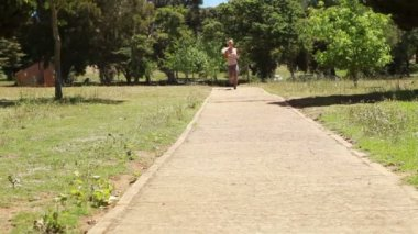 A woman jogs up a footpath towards and past the camera — Stock Video