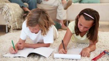 Syskon gör sina läxor på vardagsrumsgolvet med sina föräldrar bakom dem — Stockvideo