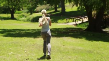 A woman jogs in the park away from the camera — Stock Video
