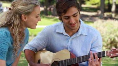 Un ragazzo suona la chitarra per la sua ragazza come si guardano a vicenda — Video Stock
