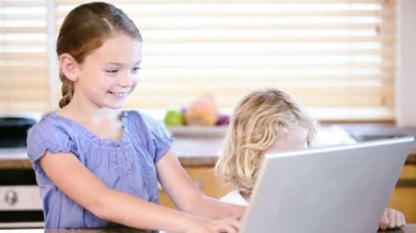 Young girl using a laptop with her brother — Stock Video