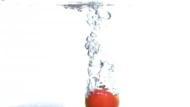 Tomato submerged into water in super slow motion — Stock Video