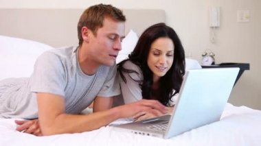 Couple using laptop on their bed — Stock Video