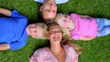 Overhead shot of a family smiling as they lie head to head in grass — Stock Video