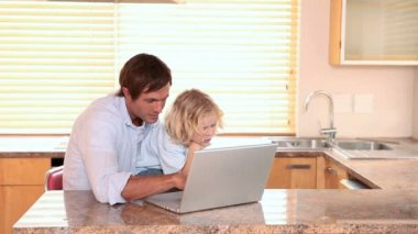 Father and son using a laptop together — Stockvideo