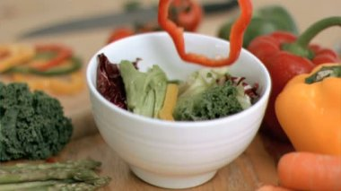 Vegetables dropping into bowl in super slow motion — Stock Video