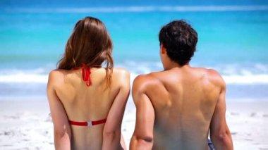 Couple sitting while sunbathing — Stock Video