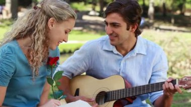 Boyfriend plays guitar for his girlfriend as she holds a rose and then kiss — Stock Video
