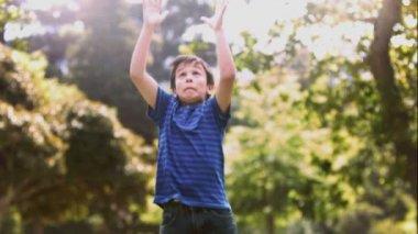 Niño jugando en cámara lenta con un balón de rugby — Vídeo de Stock
