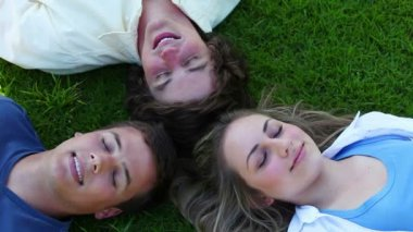 Three friends lying head to head before opening their eyes and smiling — Stock Video