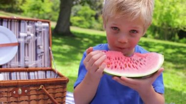 A boy looks at the camera while biting a watermelon before swallowing and smiling — Stock Video