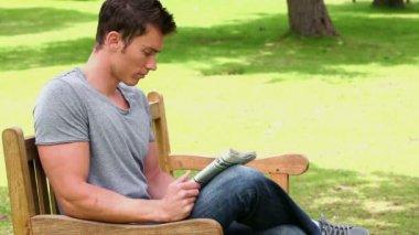 Hombre leyendo un periódico mientras está sentado en un banco de madera — Vídeo de Stock