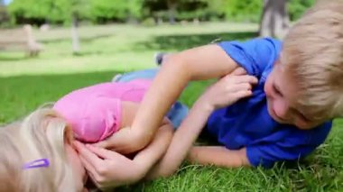 Boy and a girl tickling each other on the grass — Stock Video
