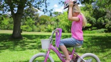 Kız bir bisiklet kask koyar ve tutamaç çubukları tutar — Stok video
