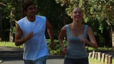 A smiling couple look to one another as they jog — Vídeo Stock