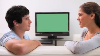 Couple talking in front of the television — Stock Video