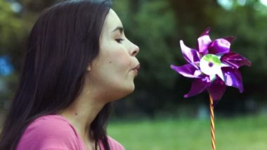 Woman breathing on a pinwheel in slow motion — Stock Video