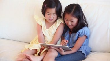 Two girls happily looking at a tablet computer — Stock Video