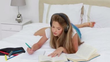 Young woman listening to music while doing her homework — Stock Video