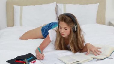 Young woman studying while listening to music — Stock video