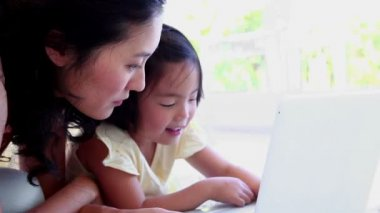 Mother using a laptop with her daughter — 图库视频影像