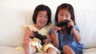 Two sisters playing a games console together — Vídeo de Stock