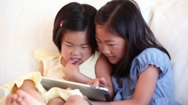 Two girls laughing while using a tablet computer — Stock Video
