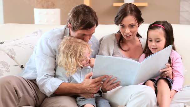 Familia sonriente, leer un libro juntos — Vídeo de stock