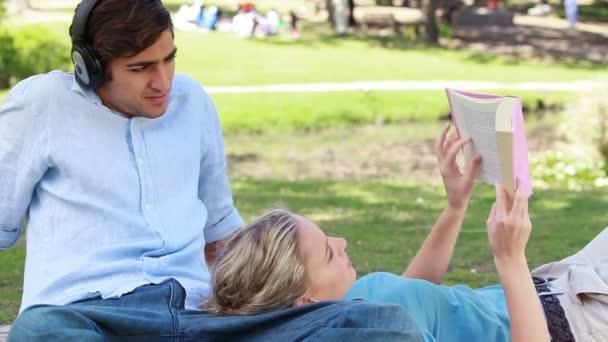 Un hombre escucha con auriculares como una chica se encuentra en sus piernas y Lee su libro — Vídeo de stock