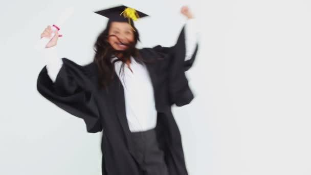 Estudiante graduado feliz lanzando su gorra — Vídeo de stock