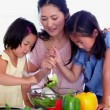 Children helping their mother mix a salad — Stock Video