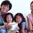 Family watching television while eating popcorn — Stock Video