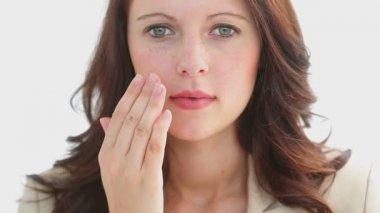 Serious brunette massaging her cheek — Stock Video