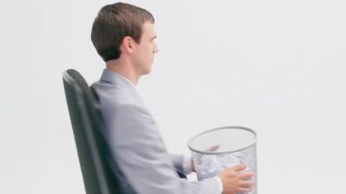 Businessman sitting while holding a wastebasket — Stock Video