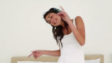 Brunette haired woman dancing while listening to music — Stock Video