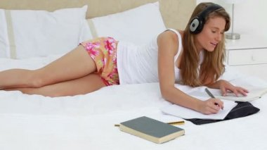 Happy young woman listening to music while studying — Stock Video