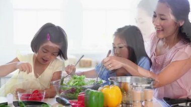 Family work together to make a salad — Stockvideo