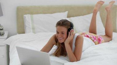 Donna gioiosa ascoltando musica davanti al suo portatile — Video Stock