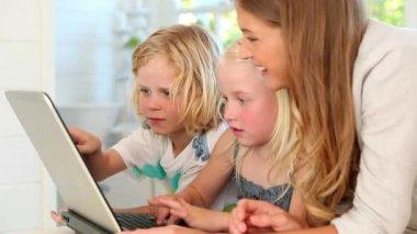 Mère à l'aide d'un ordinateur portable avec ses enfants — Vidéo