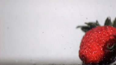 Water in super slow motion falling on red fruits — Stock Video