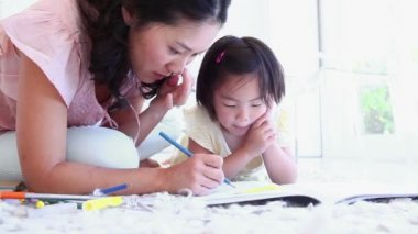 Mother helping her daughter with colouring in a living room