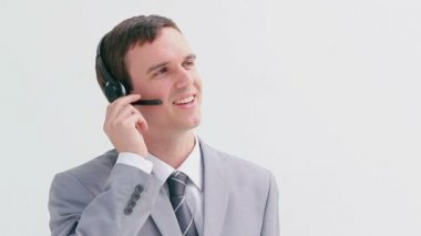 Smiling call centre agent talking into his headset — Stock Video