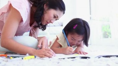 Mother looking at her daughter as she colours in a living room