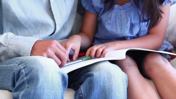 Fille d'un livre sur ses genoux des pères à colorier — Vidéo