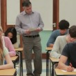 Students doing a test while teacher walk arround — Stock Video