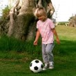 Stock Video: Child dribbling with football