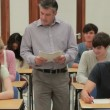 Stock Video: Teacher collecting tests